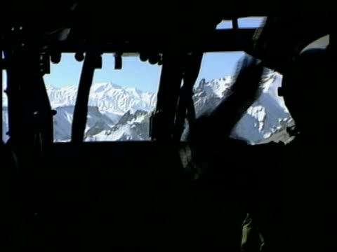 john irvine view over snow covered mountains of afghanistan int helicopter bv pilot at controls in cockpit of military helicopter ext air view shadow... - itv late news stock-videos und b-roll-filmmaterial