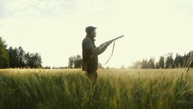 Hunter gets ready to shoot a weapon at golden hour