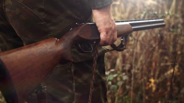 ein jäger geht vorsichtig durch das schilf mit seinem gewehr in der hand, während er seine beute streift. lager vide - wapiti stock-videos und b-roll-filmmaterial