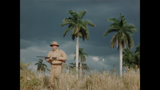 Hunter Walks Holding Rifle Through Tall Grass