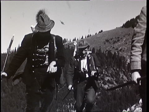 1937 b/w montage hunters coming back from hunt in mountains, carry deer / tyrol, austria - alpi video stock e b–roll