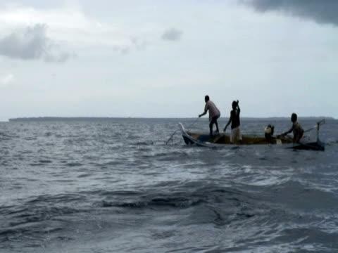 hunters on boat harpooning leatherback turtles, kei islands, indonesia - arpone video stock e b–roll