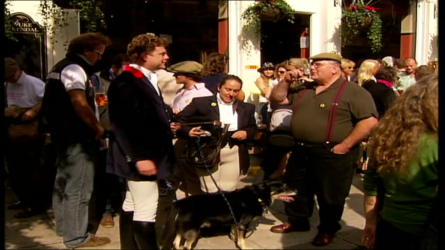 connaught square squirrel hunt england london ext hunting supporters outside pub zoom in man and woman petting small dog huntsman dressed in navy... - lager stock videos & royalty-free footage