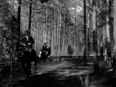huntsman carl lightfoot on horseback blowing horn, vs hounds leading 'the field' through woods, horses jumping felled log, down trail. vs fox hounds... - 金管楽器点の映像素材/bロール
