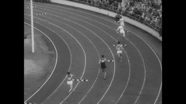 Hurdlers start race and head into first turn during Summer Olympics competition / pan two runners in distance / home stretch with American Charles...