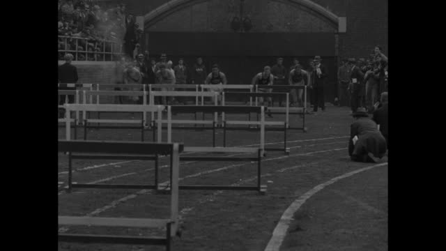 MS hurdles on racetrack people on field at Franklin Field / CU John McHugh fires starting gun for hurdle race / racers jumping hurdles / MS...