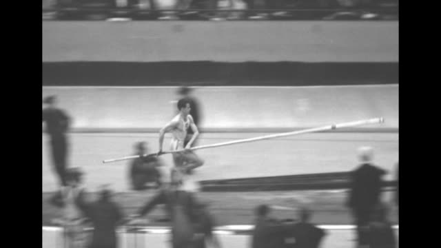 Hurdles race with one AfricanAmerican racer participating / Earle Meadows pole vaults and VO crowd cheers as mile racers run by in bg / in the...