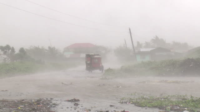 hurricane force winds and torrential rain lash motorbike taxi in aparri, philippines. super typhoon megi or juan, ne luzon, philippines oct 2010 / audio - record breaking stock videos & royalty-free footage