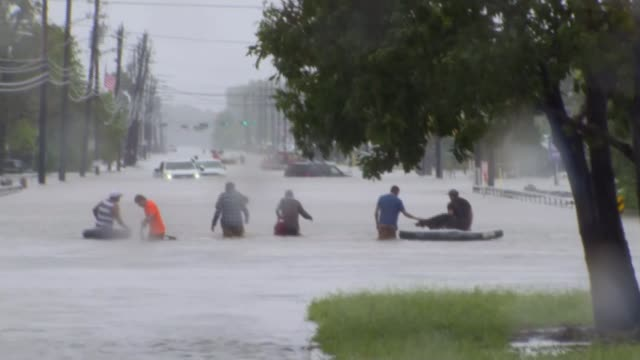 hurricane harvey now a tropical storm returns to land in louisiana after devastating texas houston people wading along flooded road the same road now... - hurrikan stock-videos und b-roll-filmmaterial