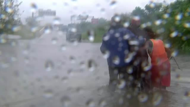 Hurricane Harvey now a Tropical Storm returns to land in Louisiana after devastating Texas EXT Various of reporter helping blind man along through...