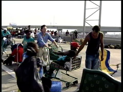 aftermath: rescue operation; queues of survivors from hurricane katrina waiting to be rescued rugman along pushing lisa johnson in supermarket trolley - 救う点の映像素材/bロール