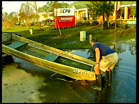 vidéos et rushes de slidell: effects on middle classes; usa: louisiana: slidell: ext piece of twisted corrugated iron in road and flattened house behind gv boat marooned... - turning on or off