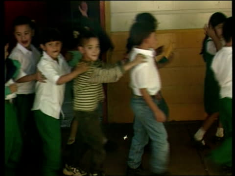 hurricane mitch four months on a special report honduras tgv line of children towards arriving at school and shouting hello sot gv class as teacher... - 女性教師点の映像素材/bロール