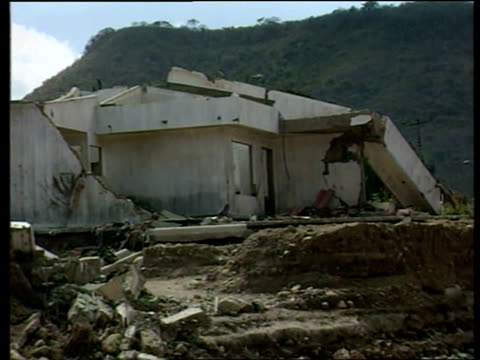 hurricane mitch four months on - a special report; tgv narrow muddy river : gv wrecked buildings, ruined by hurricane mitch with river in foreground:... - major road stock-videos und b-roll-filmmaterial