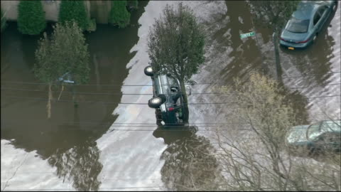 hurricane sandy flooding staten island aerials car flipped on side in flooded road - environment or natural disaster or climate change or earthquake or hurricane or extreme weather or oil spill or volcano or tornado or flooding stock videos & royalty-free footage