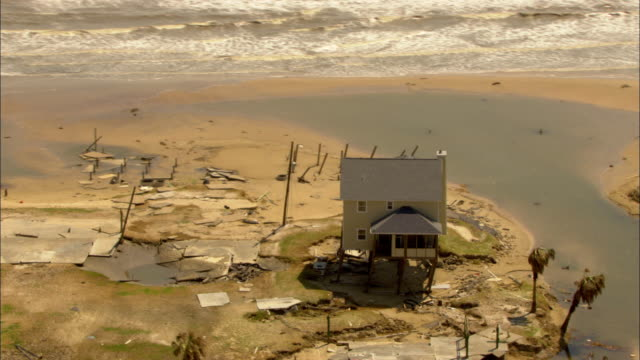 hurricane-damaged houses on stilts are seen from the air. - stilts stock videos and b-roll footage