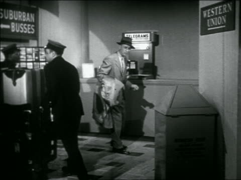 "vídeos y material grabado en eventos de stock de b/w 1956 hurried man in bus station talking to black porter + approaching phone marked ""telegrams"" - maletero"