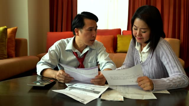 mann und seine frau, seine rechnungen zu berechnen, während seine familie auf dem sofa. ernst mit finanziellen problem. - paar mittleren alters stock-videos und b-roll-filmmaterial