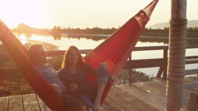 MS Husband and wife couple together in hammock watching sunset