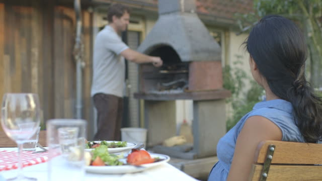 vidéos et rushes de husband and wife enjoying in domestic garden - chaise