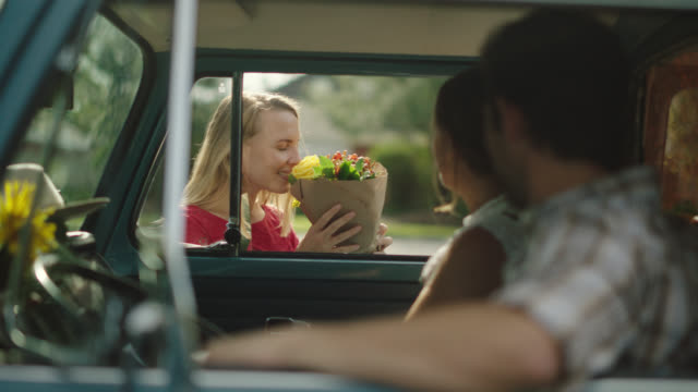 vidéos et rushes de husband and wife florists delivery flowers, young woman and her dog come up to say hello and smells bouquet - bouquet de fleurs