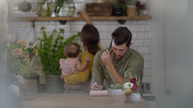 husband and wife flower shop owners struggle to work with their baby, husband tries to write down order - flower shop stock videos & royalty-free footage