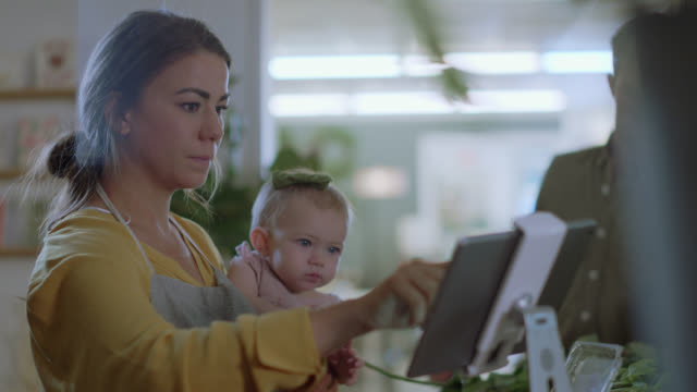 husband and wife flower shop owners struggle to work with their baby, wife works on tablet - fioraio negozio video stock e b–roll