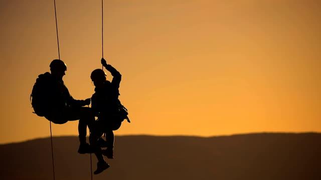 vidéos et rushes de mari et femme sur une équipe d'escalade de corde sur le sommet dans le coucher du soleil - suspendre