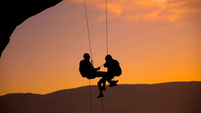 mann und frau auf einem seil kletterteam auf dem gipfel bei sonnenuntergang - klippe stock-videos und b-roll-filmmaterial
