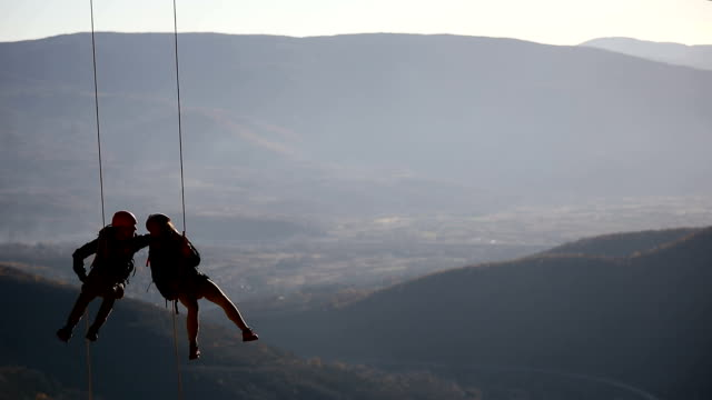 husband and wife on a rope climbing team on the summit - flexibility stock videos & royalty-free footage