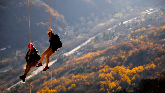 husband and wife on a rope climbing team on the summit - balance stock videos & royalty-free footage