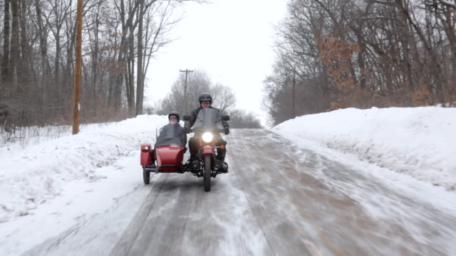 MS  POV Husband and wife ridding on motorcycle with sidecar in rural area during winter / Osceola, Wisconsin, United States