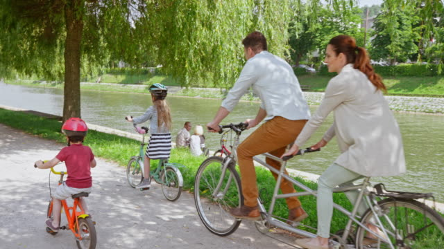slo mo cs husband and wife riding a tandem bike in the park and their two children riding alongside them - tandem stock videos & royalty-free footage