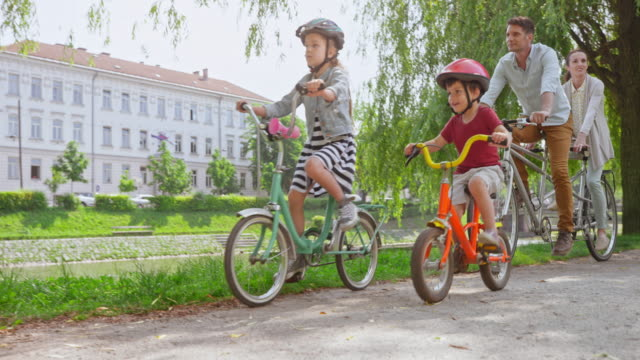 cs husband and wife riding a tandem bike in the park and their two children riding alongside them - two parents stock videos & royalty-free footage