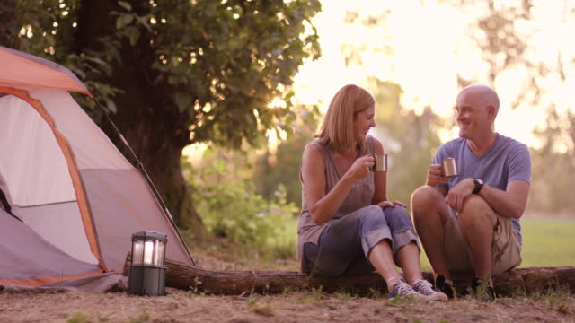 Husband and wife sipping coffee while camping outdoors