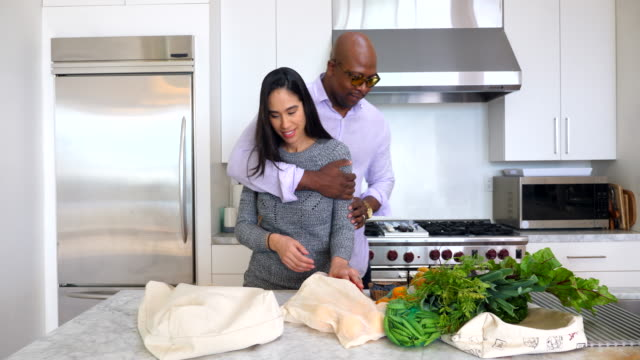 ms husband embracing wife while putting away groceries in kitchen - reusable bag stock videos & royalty-free footage