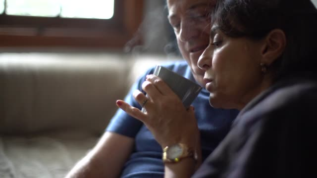 Husband embracing wife with fever while drink her hot tea
