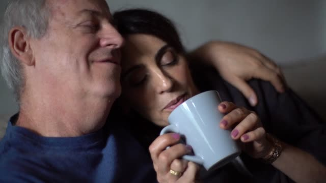 vídeos de stock e filmes b-roll de husband embracing wife with fever while drink her hot tea - casal casado