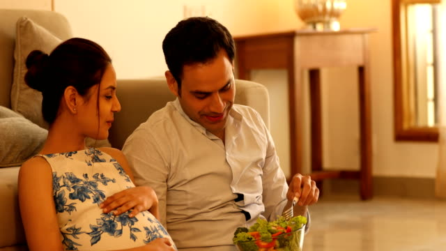 MS Husband feeding salad to his pregnant wife while sitting in living room / India