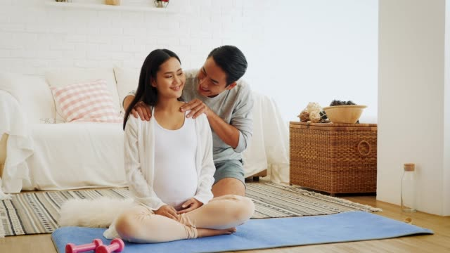 Husband giving his pregnant wife back and shoulder massage after training yoga or exercise at home, Health and pregnancy concept