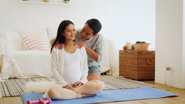 vidéos et rushes de mari redonner sa femme enceinte et les épaules massage après formation yoga ou l'exercice à la maison, concept santé et grossesse - massage femme enceinte
