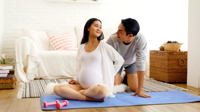 vidéos et rushes de son mari donne sa femme enceinte massage après formation yoga ou l'exercice à la maison, concept santé et grossesse - massage femme enceinte