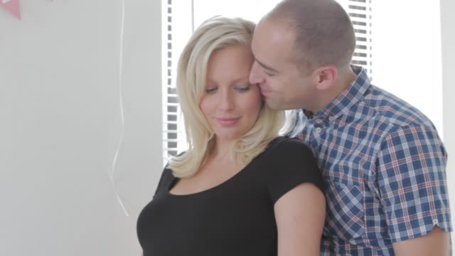 MS TD Husband giving kiss his pregnant wife and his hands caressing her belly / Sunnyside, Queens, New York, United States
