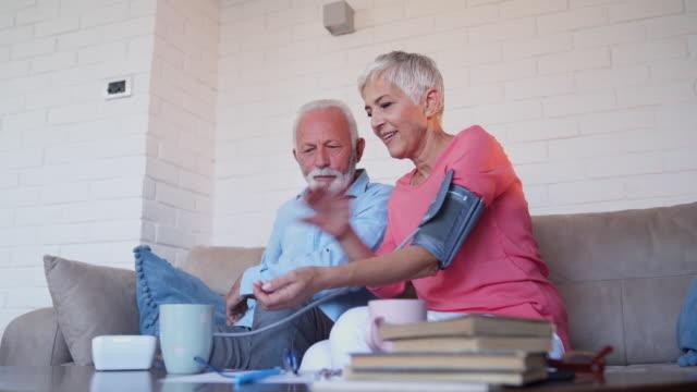 husband helping to his wife to measure blood pressure - blood pressure gauge stock videos & royalty-free footage