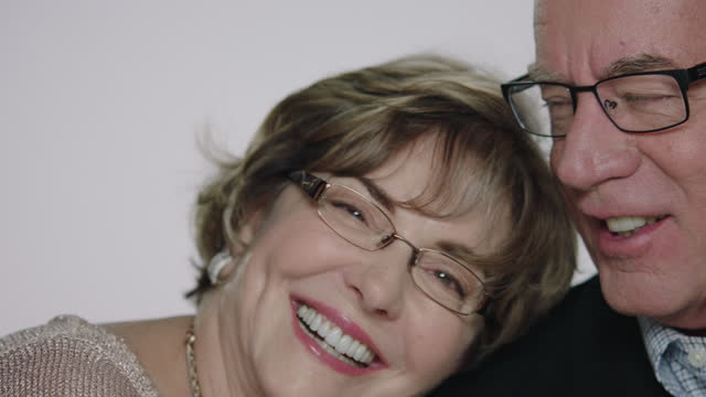 CU SLO MO. Husband laughs with wife as she leans her head on his shoulder in white studio.