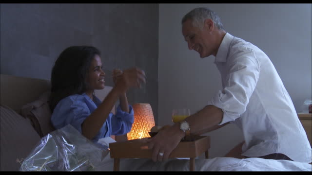 A husband serves a tray of breakfast to his wife in bed.