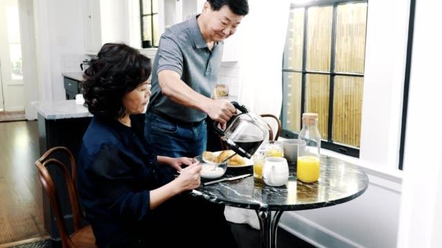 vídeos de stock, filmes e b-roll de marido que sere a esposa um copo do café - sala de café da manhã