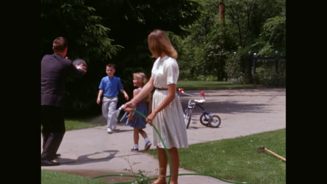 WS Husband shows wife how to water lawn as their children playing in background / United States