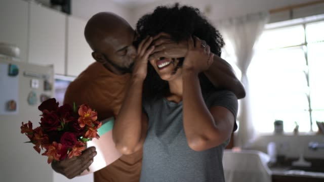 husband surprising his wife with flowers and present at home - boyfriend stock videos & royalty-free footage