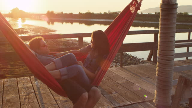 vídeos de stock, filmes e b-roll de ms husband swinging wife in hammock on dock at sunset both laughing - rede de dormir